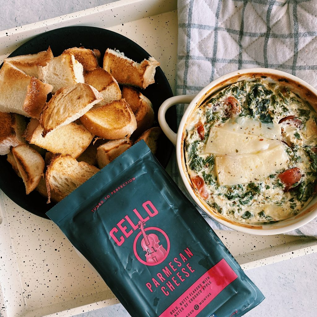 Flat lay of toasted bread with Healthier Hot Spinach Dip and full block of cheese