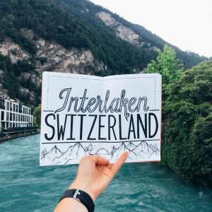 Interlaken Switzerland Lettering on white sheet of paper with scenic river in background