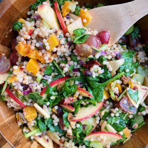 Overhead close up image of harvest salad being mixed with a wooden spoon