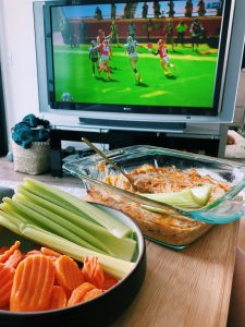 Buffalo Chicken dip in a pyrex dish on coffee table with football in the background