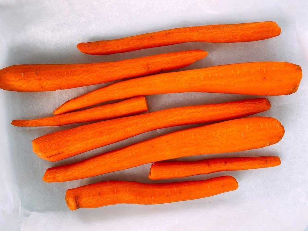 freshly peeled carrots laying on parchment paper