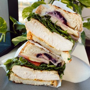 leaning tower of stacked sandwiches wrapped in parchment paper with greenery background