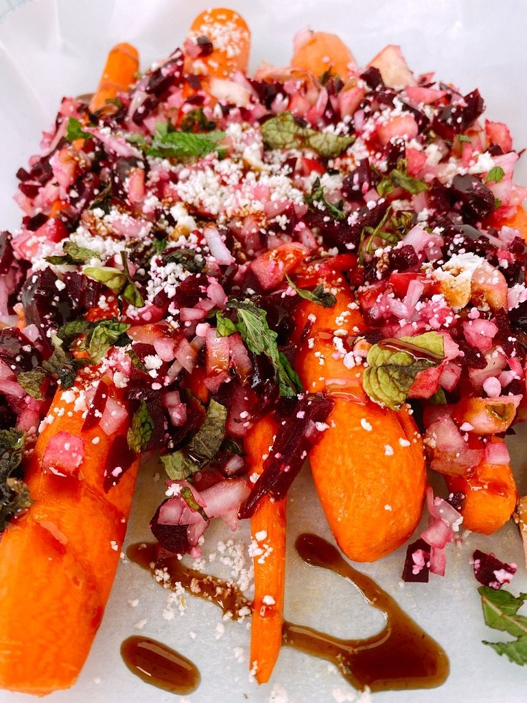 freshly peeled carrots topped with balsamic drizzle and slaw topping with white background