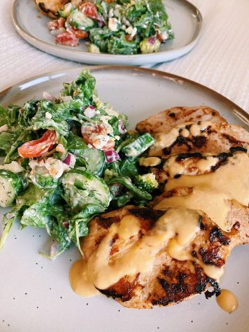two fully dressed dinner plates with a colorful salad and sliced pork tenderloin, drizzled with hummus dressing