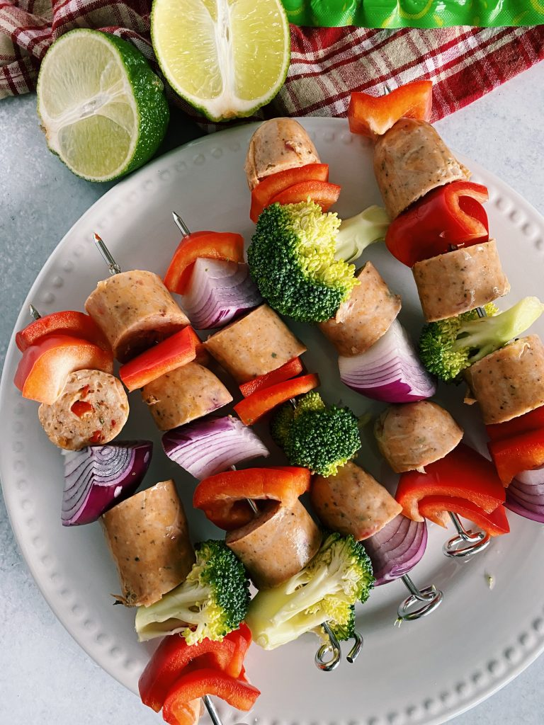 Overhead image of assembled kabobs on white plate with fresh limes as garnish