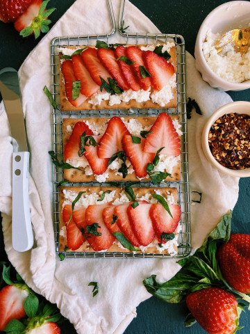 overhead flay lay shot of 3 crackers with crumbles of cheese topped with thin sliced strawberries with basil garnish all laying on top of metal wire rack