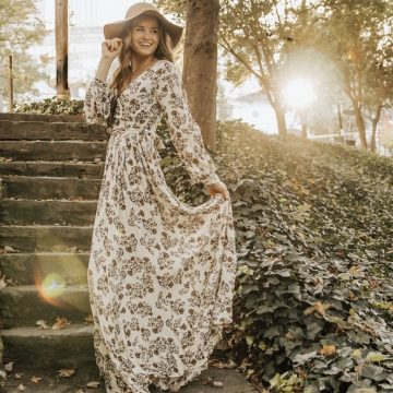 girl in sundress laughing in park with sun peaking through trees