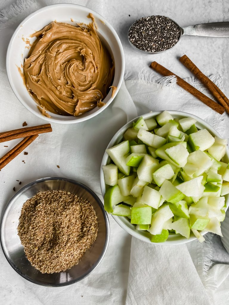 There's a bowl filled with peanut butter, flaxseed, rolled oats, and diced apples. There's a tablespoon filled with chia seeds and cinnamon sticks sitting around.