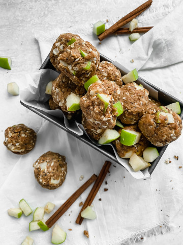 A pan is lined with parchment paper and filled with apple peanut butter energy bites. There are more energy bites, diced apples, and cinnamon sticks scattered around the pan.
