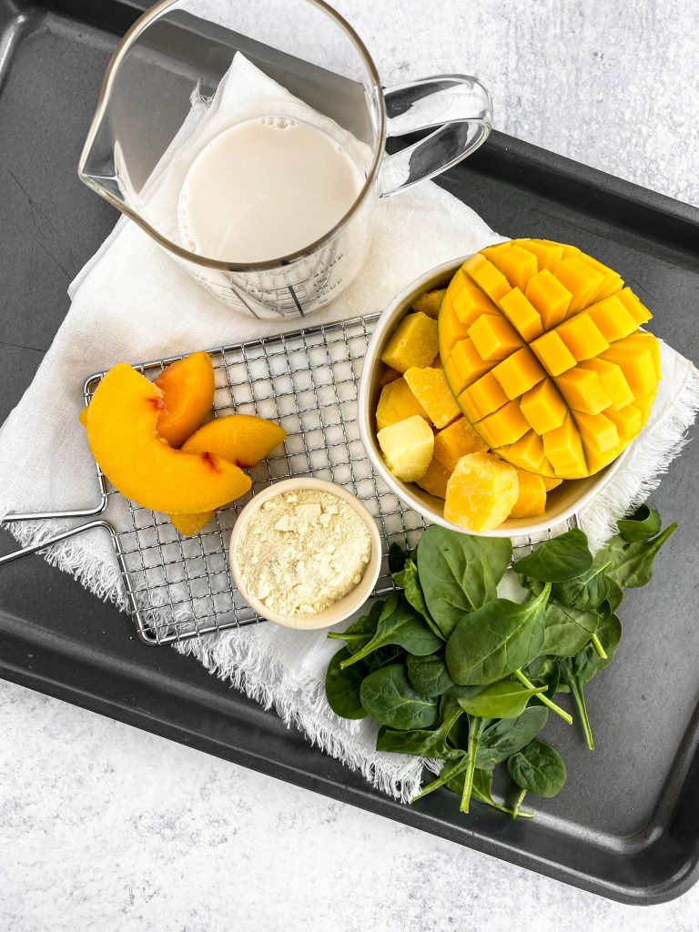 overhead image of ingredients: mango, spinach, almond milk, and protein powder