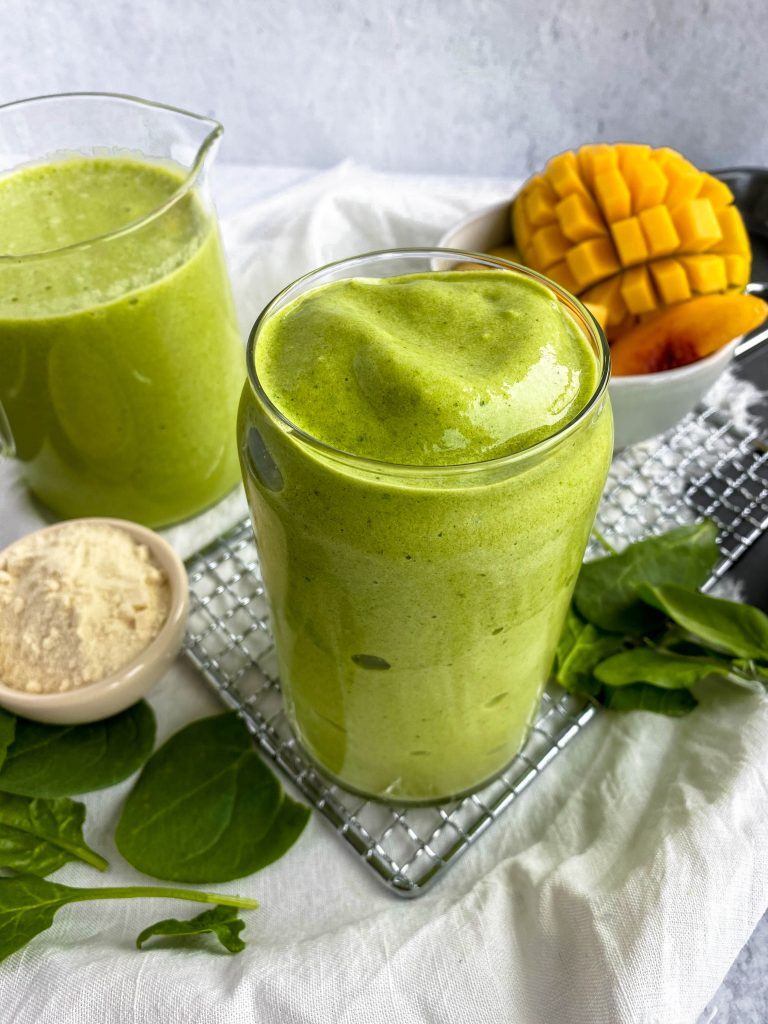 full glass of green smoothie with extras in the background and fresh mango