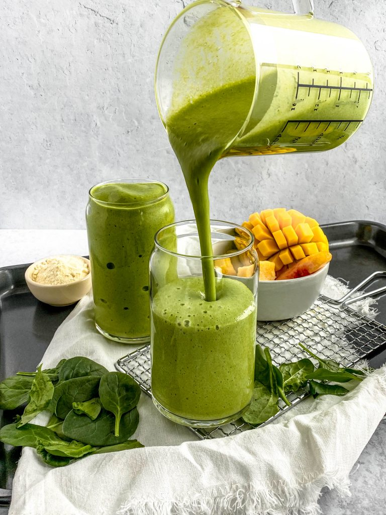action image of green smoothie pouring into half full glass with fresh mango in the background