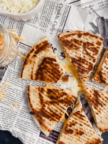 A cheesy quesadilla is sliced into six pieces with melty cheese oozing out. There is more shredded mozzarella and cheddar in the background.