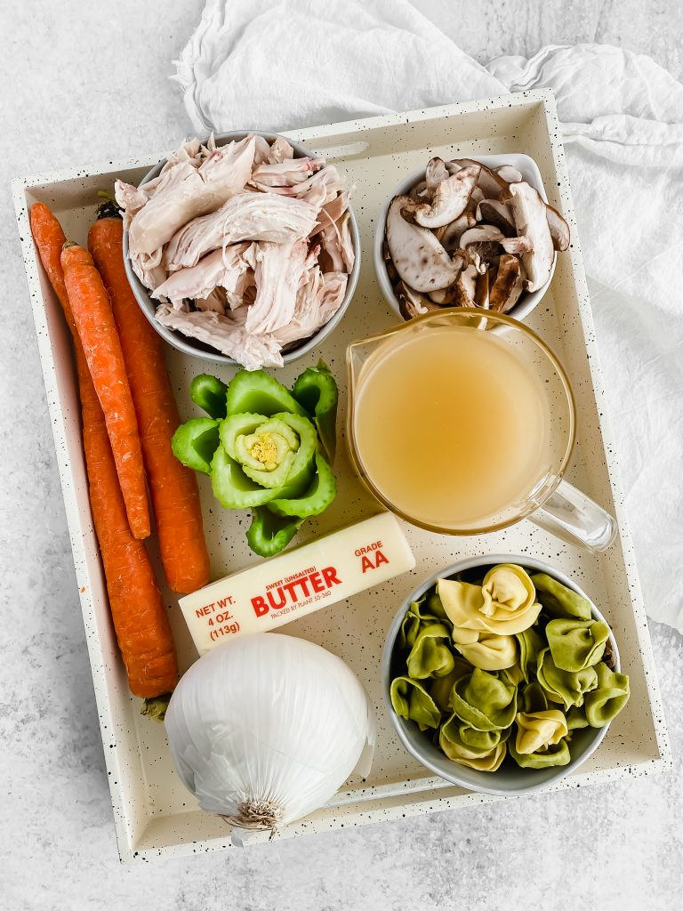 A wood tray is filled with ingredients for chicken tortellini soup. There are three carrots, celery, a white onion, a stick of butter, sliced mushrooms, shredded chicken, broth, and cheesy tortellini.