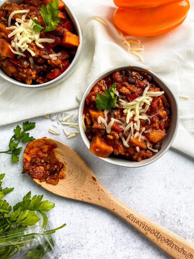 overhead image of two bowls of chili, wooden spoon on concrete background and peppers