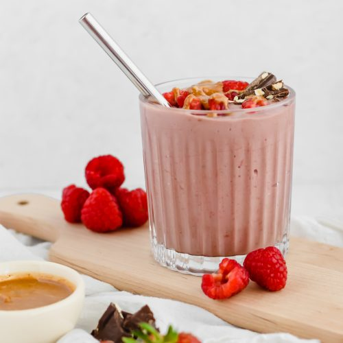 A chocolate raspberry smoothie in a glass tumbler is garnished with fresh raspberries, chocolate, and hazelnut butter drizzled overtop. The smoothie sits on a wood board with more raspberries beside it. A bowl of hazelnut butter, some chocolate pieces, and fresh strawberries sit to the side.
