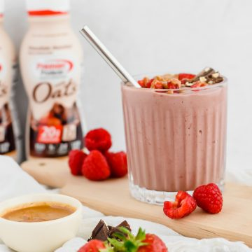 A chocolate raspberry smoothie in a glass tumbler is garnished with fresh raspberries, chocolate, and hazelnut butter drizzled overtop. The smoothie sits on a wood board with more raspberries beside it. A bowl of hazelnut butter, some chocolate pieces, and fresh strawberries sit to the side. The hazelnut protein shake used for the smoothie sits in the background.