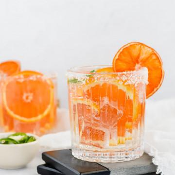 Spicy Orange and Jalapeño Margarita on a black and grey coaster