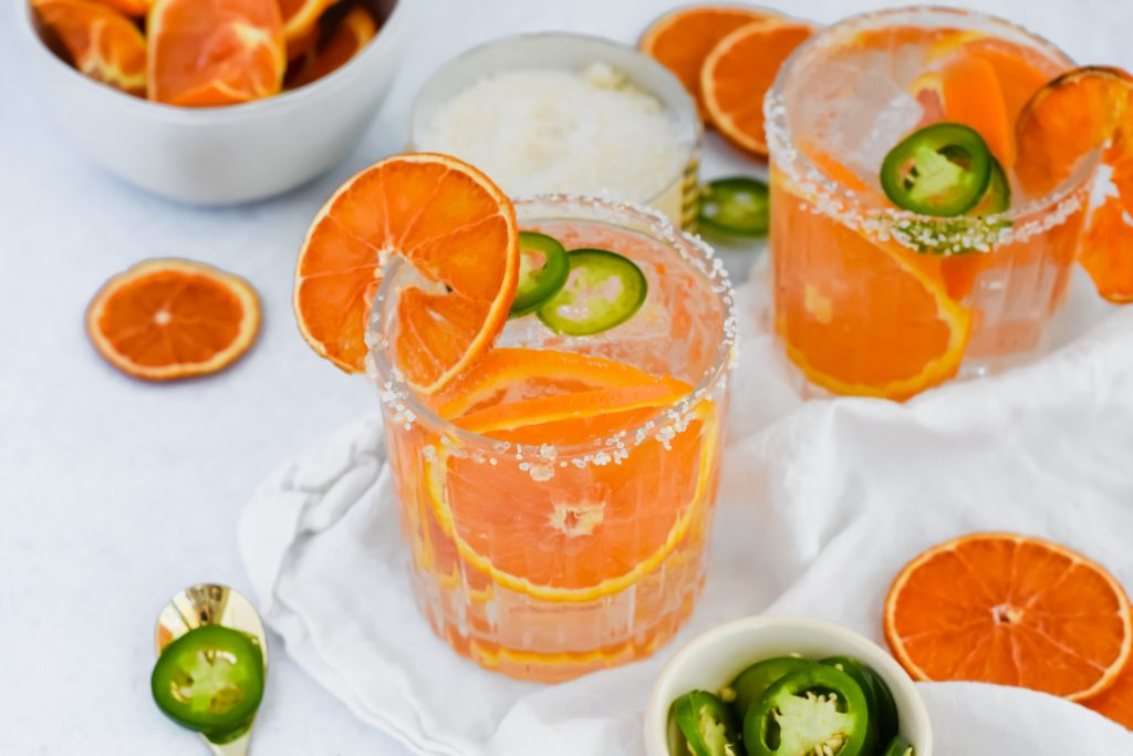 Spicy Orange and Jalapeño Margaritas surrounded by orange and jalapeno slices