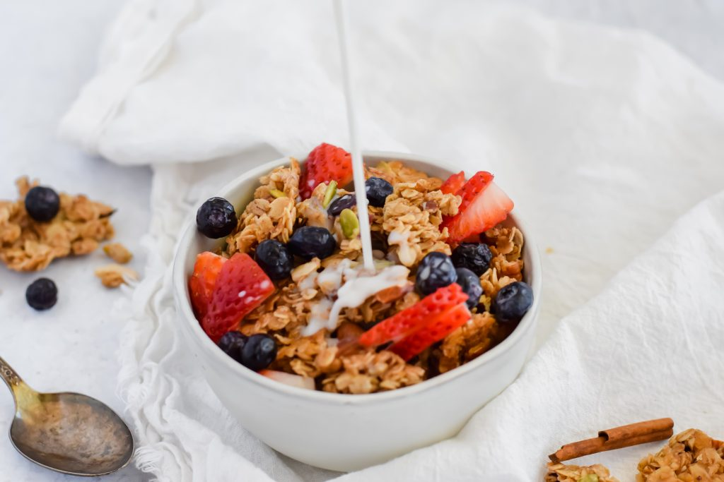 bowl of granola and fruit with milk being poured on top