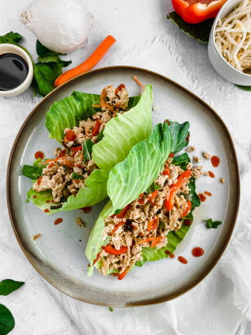 Two Thai chicken lettuce wraps sit on a ceramic plate with sriracha drizzled overtop. The wraps are filled with a chicken and vegetable mixture cooked in a soy sauce simmer. There are more veggies in the background.