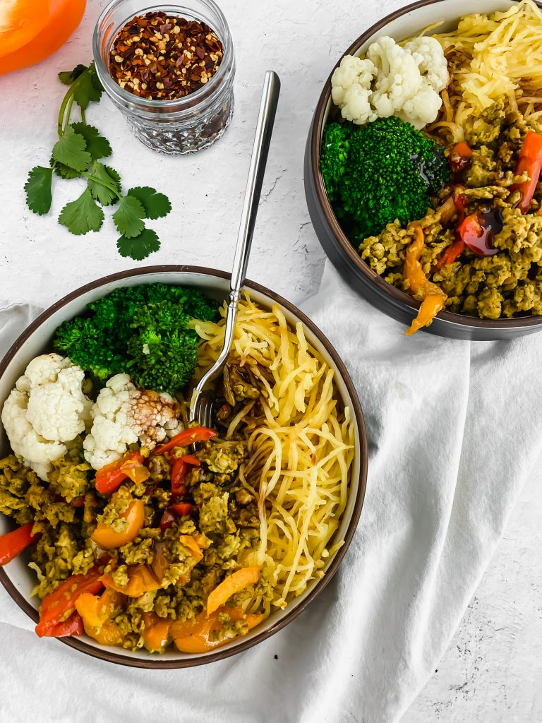 Sweet thai chicken and veggie bowls with crushed red pepper in a jar