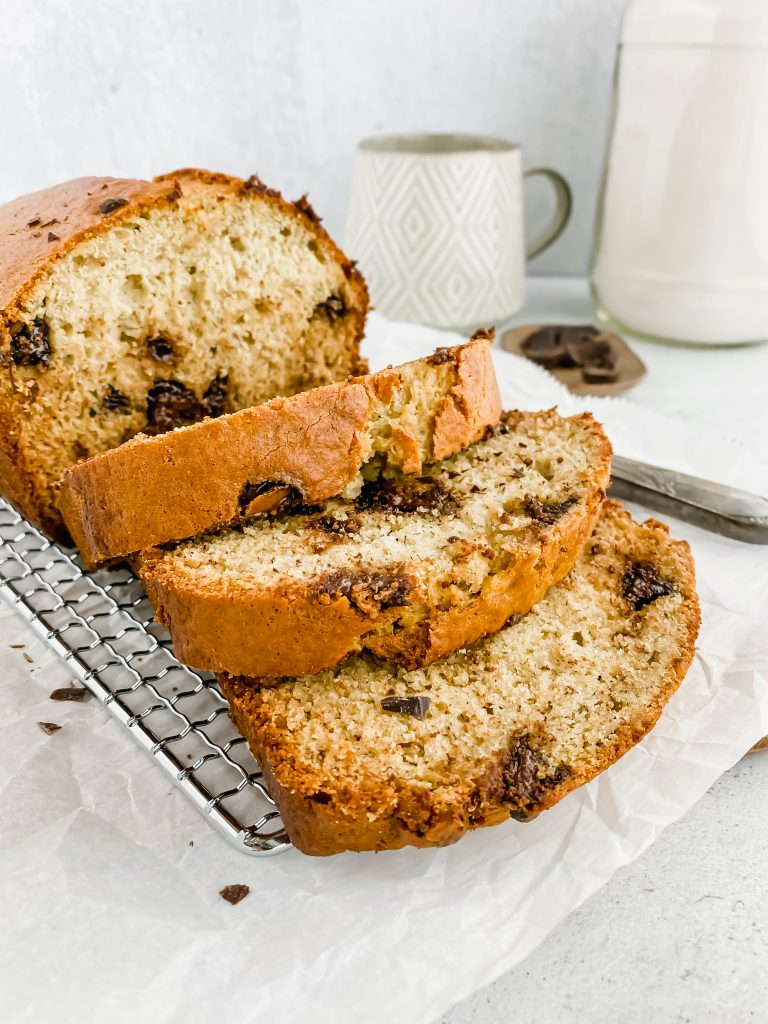 close up of sliced banana bread with loaf behind it