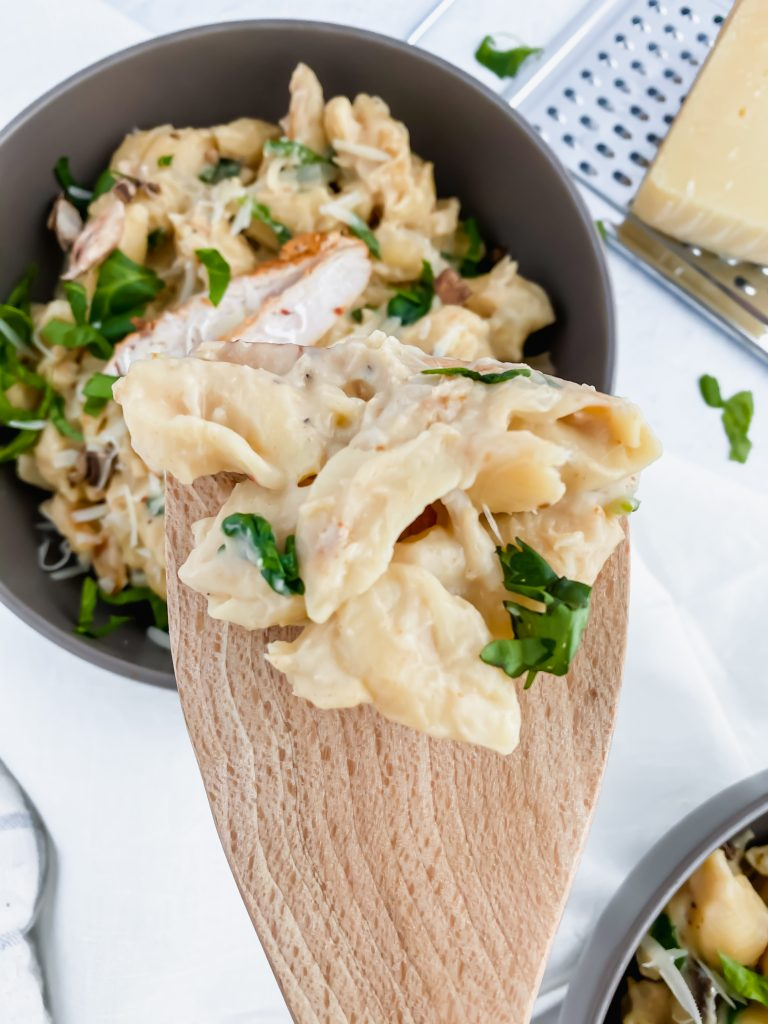 bite shot of wooden spoon with alfredo pasta on spoon
