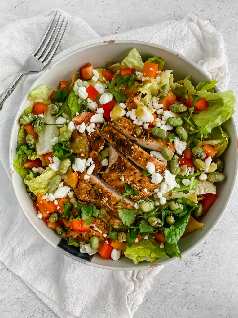 A fresh green salad is topped with sliced pieces of the best grilled chicken. There's a white linen and fork to the side.