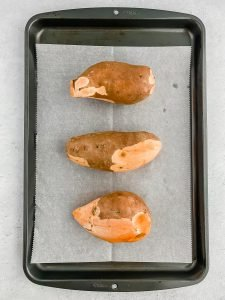 Three partially peeled sweet potatoes sit on a parchment lined baking sheet.