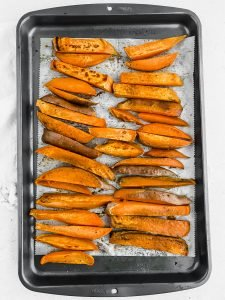 Roasted, thick cut sweet potato fries fill a parchment lined baking tray. The sweet potato fries have a nice brown char on the outside.