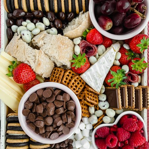 overhead image of fully assembled charcuterie board with lots of fresh berries and chocolate