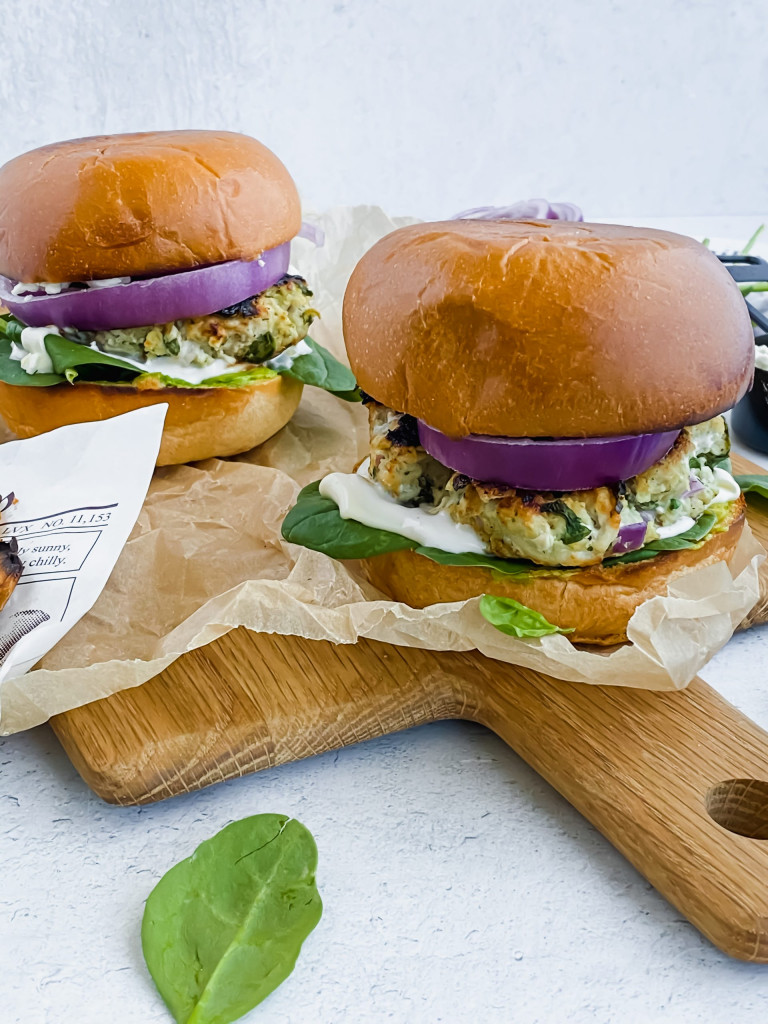 two fully loaded turkey burgers stacked up on parchment paper with concrete background