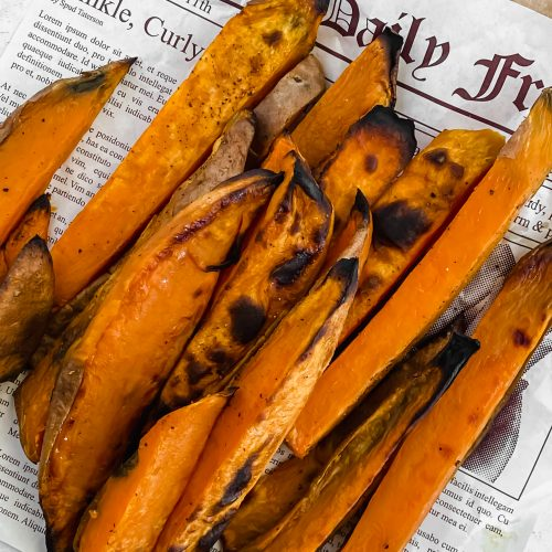 Thick sliced, roasted sweet potato fries sit on sheet of newspaper. The fries have a nice brown char on the outside.