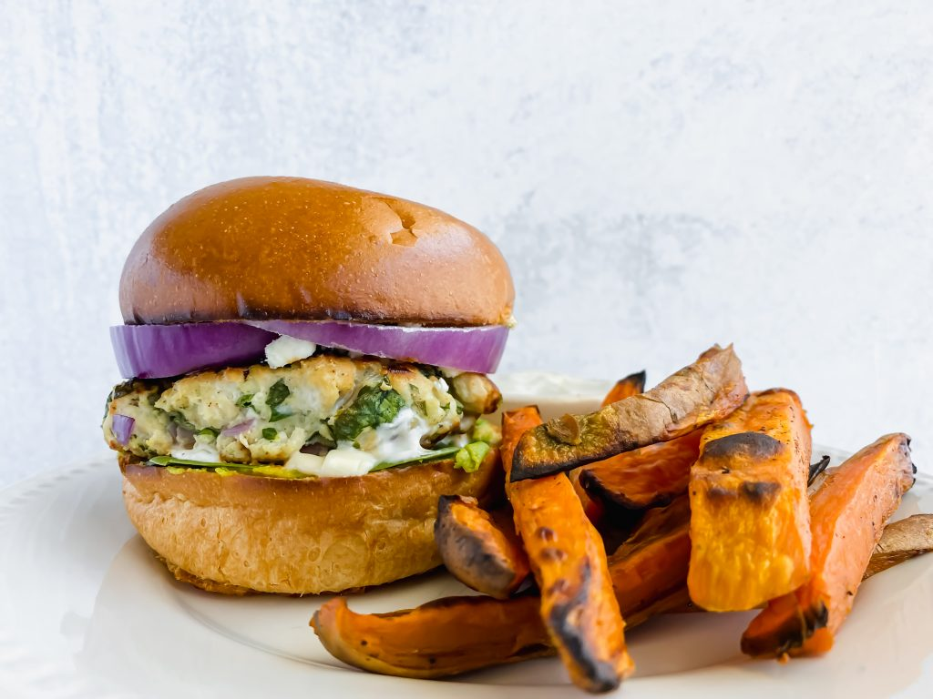 front shot of spinach ranch feta turkey burgers on a plate with sweet potato fries