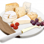 Wood slab with cheese and fruit with gold knife