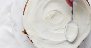 Icing a carrot cake with cream cheese frosting