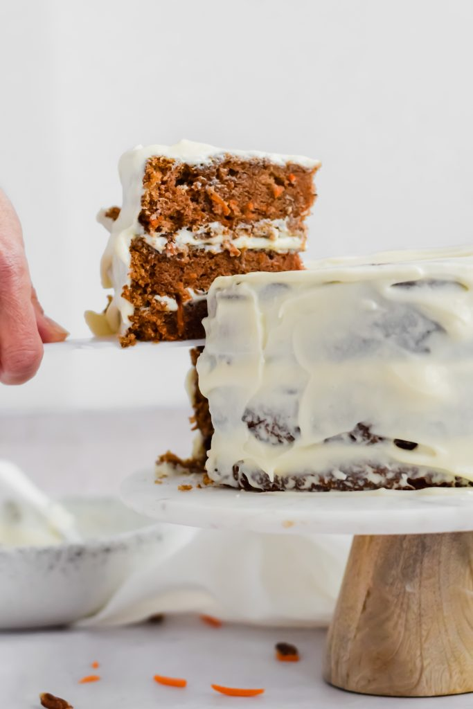 Cutting a slice of carrot cake with cream cheese frosting