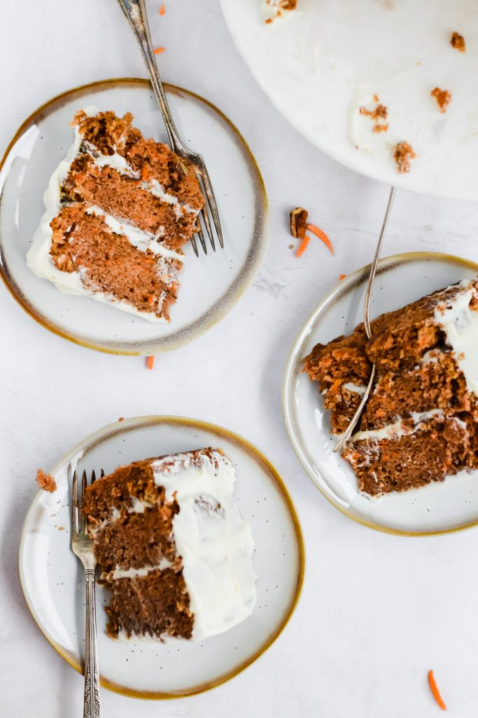 3 slices of cream cheese frosted carrot cake on a white and gold plate