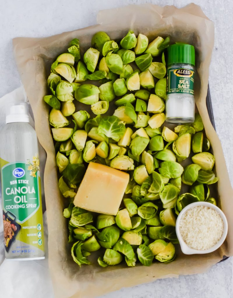 Quartered brussels sprouts on a sheet pan with a wedge of parmesan cheese, canola oil, and salt