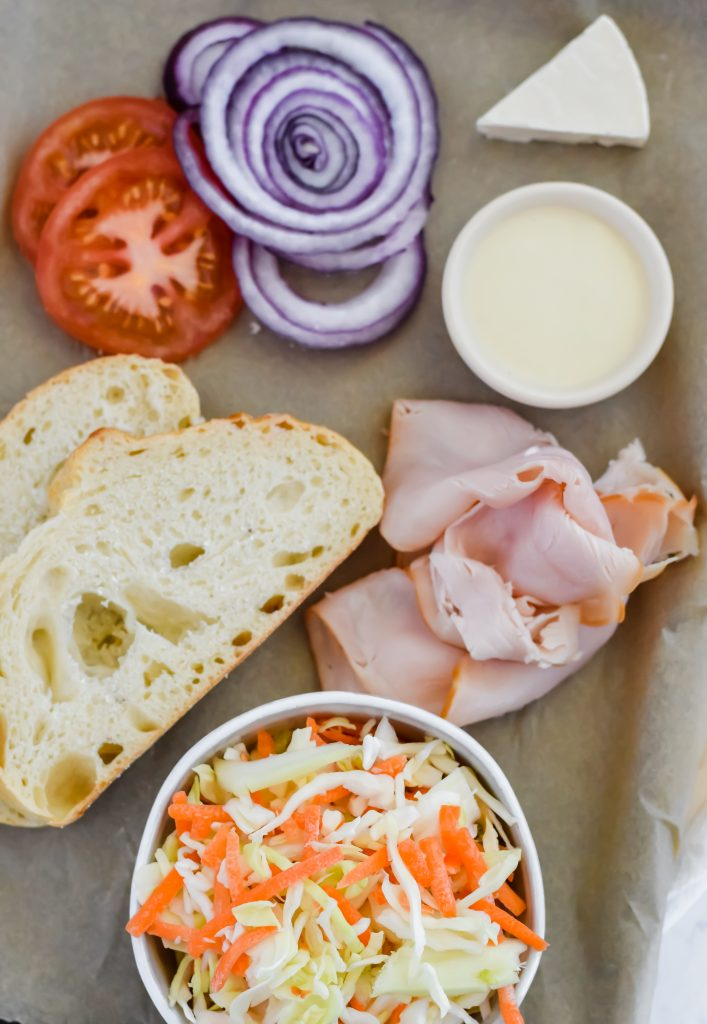 Grilled Turkey Reuben ingredients on a sheet pan including two slices of bread, tomato, red onion, dressing, cheese, turkey, and a bowl of coleslaw
