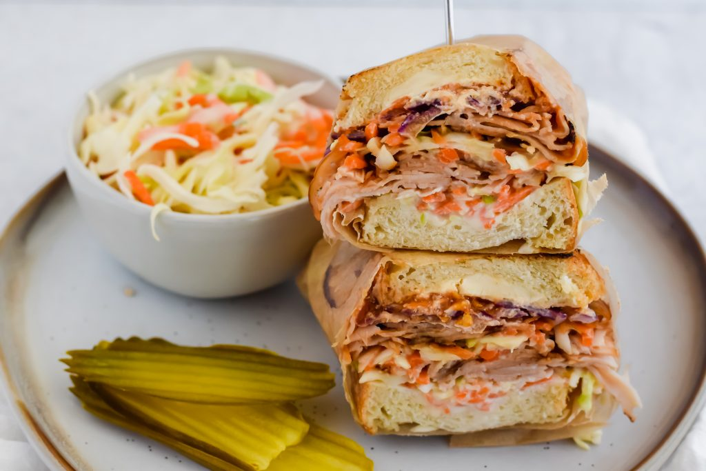Two halves of a Grilled Turkey Reuben stacked on top of each other with pickle chips and a cup of coleslaw