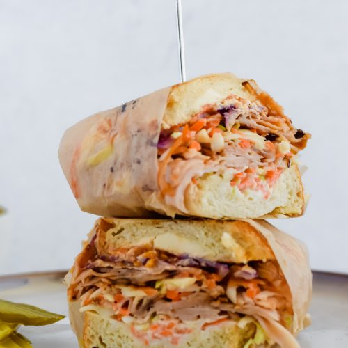 Two halves of a wrapped Grilled Turkey Reuben Sandwich stacked on top of each other