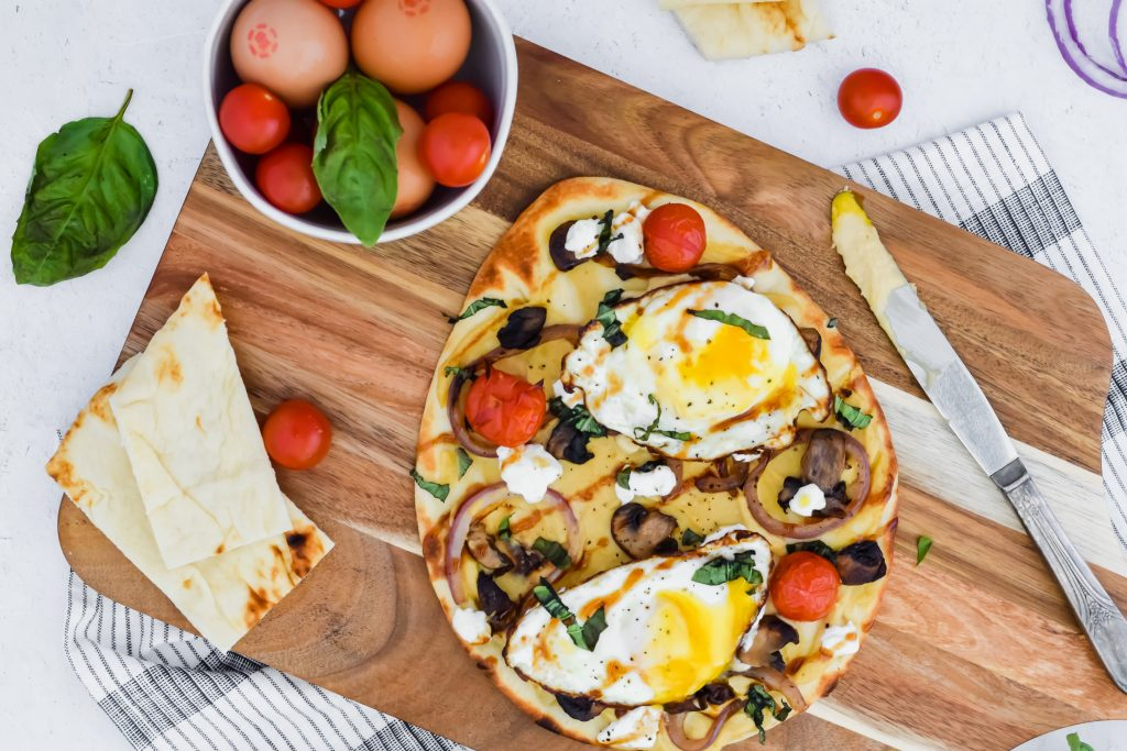 Savory Breakfast Flatbread with hummus, fried eggs, vegetables, goat cheese and balsamic glaze