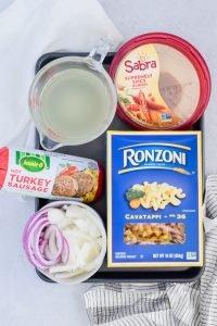 Ingredients for Spicy Sausage Hummus Pasta including pasta water, Sabra hummus, ground turkey sausage, onions, and pasta