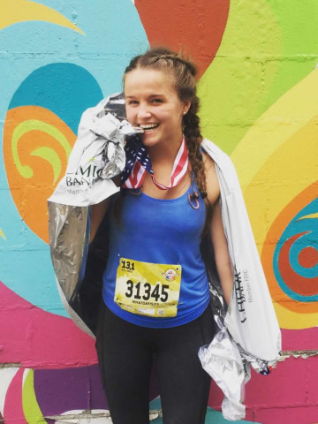 courtney after finishing half marathon race with medal on and colorful background