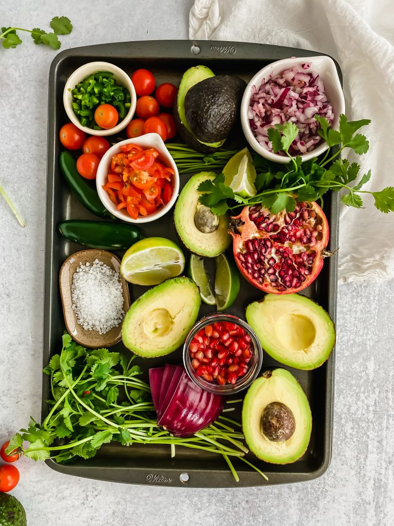 Homemade Guacamole ingredients on a sheet pan including avocado, cilantro, red onion, pomegranates, tomatoes, and salt
