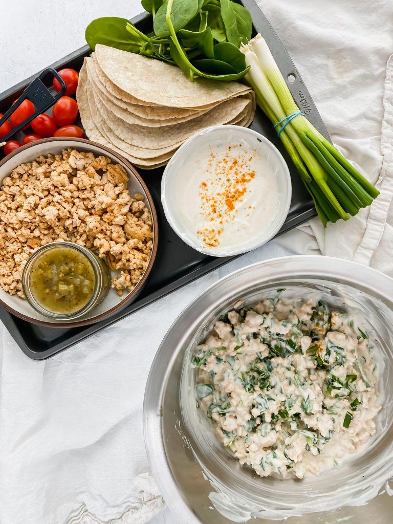 Skinny Turkey Enchilada ingredients on a baking sheet and a bowl of enchilada filling