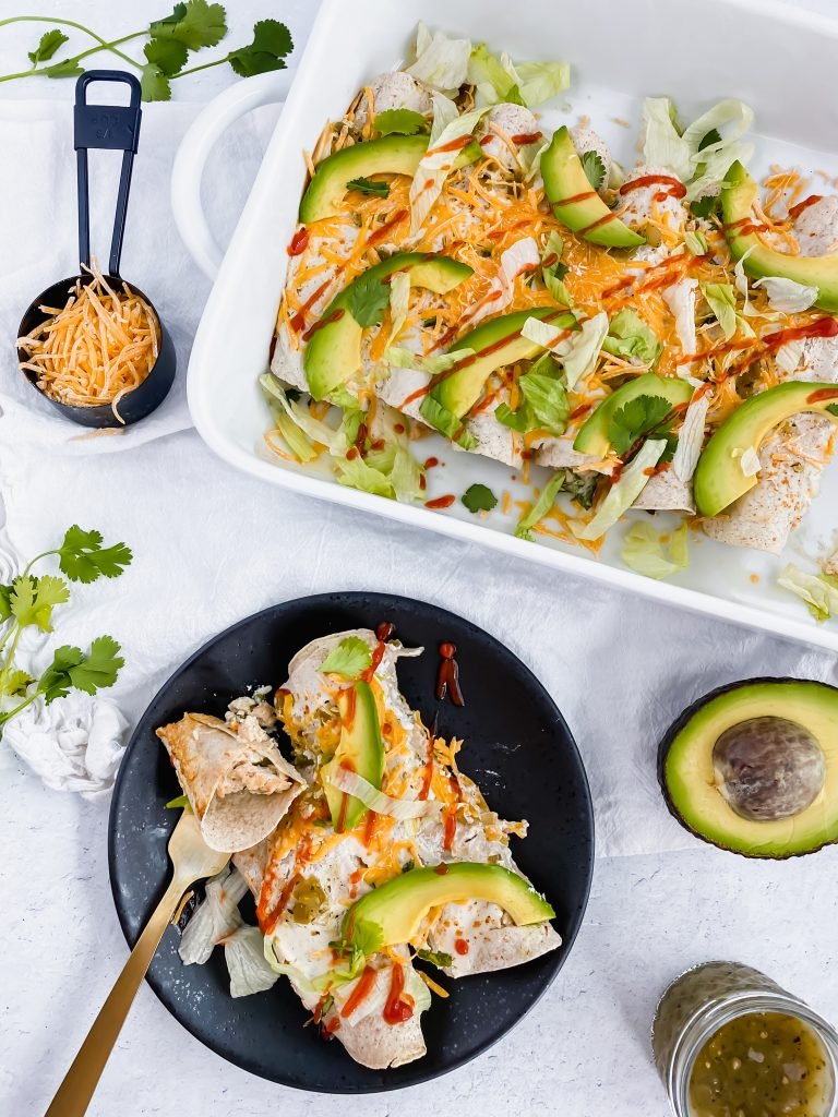 Skinny Turkey Enchiladas in a casserole dish and on a plate topped with sriracha and avocado