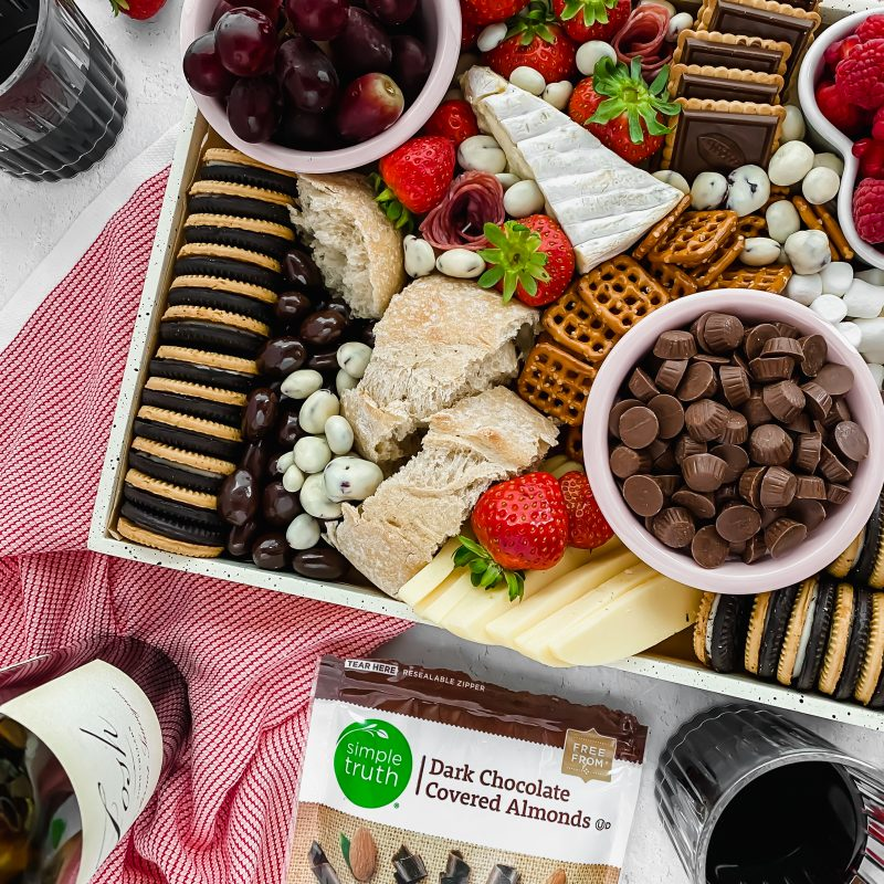 charcuterie tray filled with fruit, chocolate, and cheese with wine surrounding it